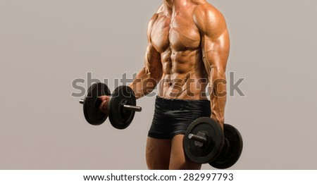 Strong bodybuilder man with perfect abs, shoulders,biceps, triceps and chest, personal fitness trainer training with heavy dumbbells, flexing his arms - stock photo