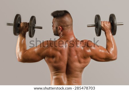 Strong bodybuilder man with perfect abs, shoulders,biceps, triceps and chest, personal fitness trainer training with heavy dumbbells, flexing his arms, getting his biceps big - stock photo