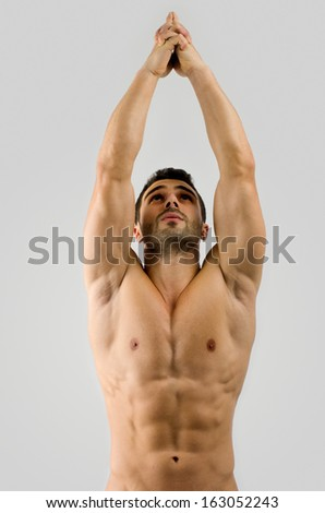 Strong bodybuilder man with perfect abs, shoulders,biceps, triceps and chest pointing up - stock photo