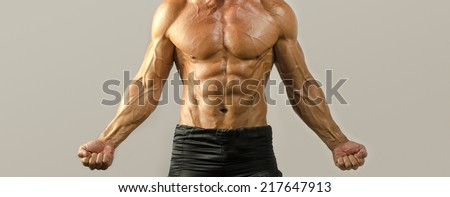 Strong bodybuilder with perfect abs, shoulders,biceps, triceps and chest, personal fitness trainer, flexing his muscles - stock photo