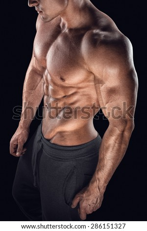 Strong bodybuilder with six pack, perfect abs, shoulders, biceps, triceps and chest. Closeup of a handsome power athletic young man with great physique.  - stock photo