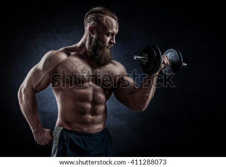 Strong bodybuilder with six pack, perfect abs, shoulders, biceps, triceps and chest. Power athletic bearded man in training pumping up muscles with dumbbell.  - stock photo