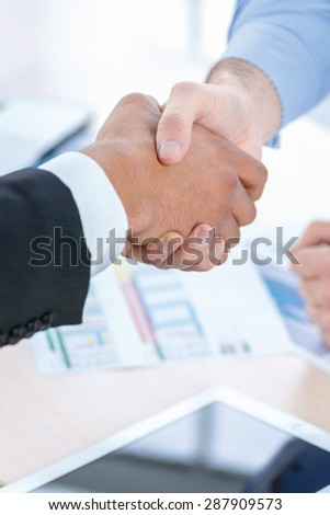 Strong business handshake. Two Confident businessman sitting at the negotiating table in the office and shaking hands close-up view of hands. Business people dressed in formal wear - stock photo