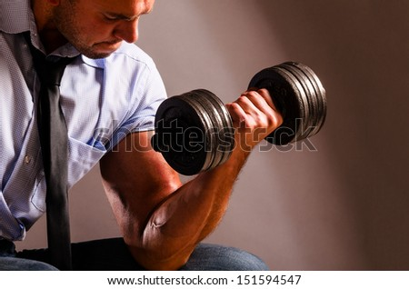 strong business man is raising a dumbbell - stock photo
