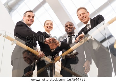 Strong business team. Low angle view of four confident business people standing close to each other and holding hands together - stock photo