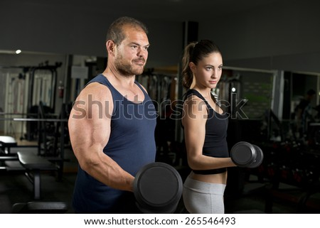 Strong coach and beauty girl at gym training biceps - stock photo