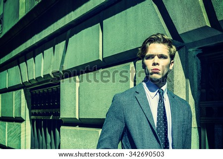 Strong color filtered look with green tint and harsh sunshine to represent young man attitude - confident, determination, success. American College Student traveling, studying in New York. City Boy.  - stock photo