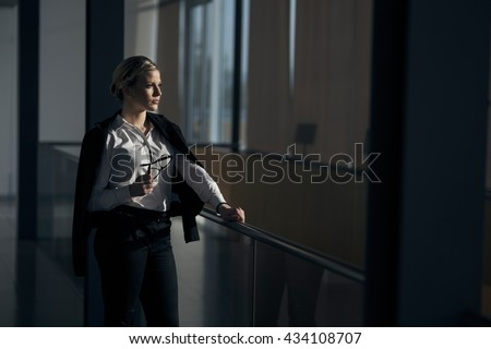 Strong, confident, business woman standing in an office building hallway - stock photo