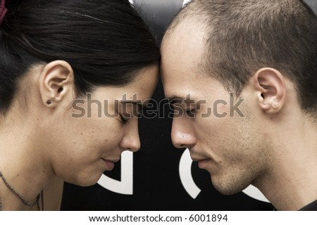 Strong connection - Portrait of a young couple head to head meditating with eyes closed - stock photo