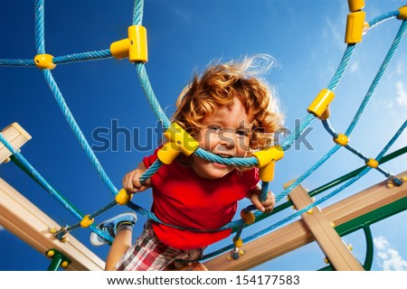Strong expression of active of happy little three years old child boy biting the rope on the playground web - stock photo