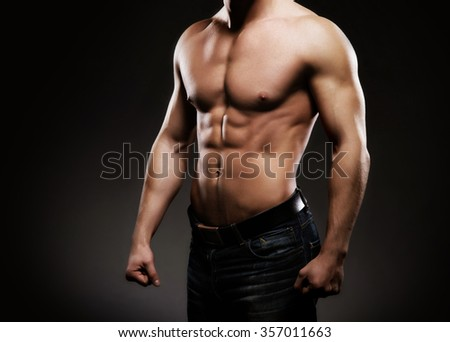 Strong, fit and sporty bodybuilder man over black background. - stock photo