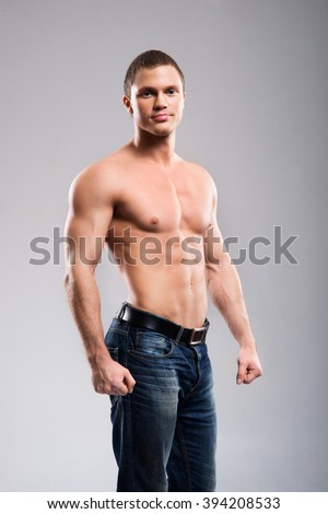 Strong, fit and sporty bodybuilder man over grey background - stock photo