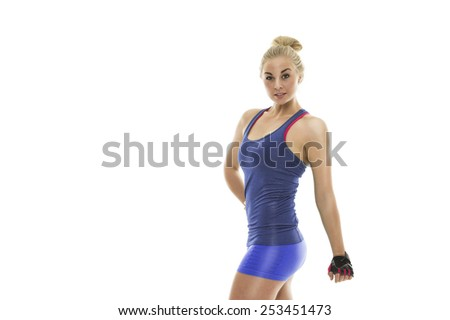 Strong fit attractive young woman in blue sportswear posing with her hand on her hip looking at the camera with a jaunty expression showing off her shapely body, isolated on white - stock photo