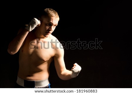 Strong fit young boxer fighting in a match standing on a dark shadowed background with his bandaged fists raised concentrating on his opponent, with copyspace - stock photo