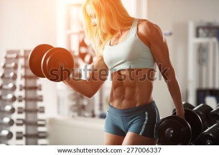 Strong fitness woman bodybuilder with white hair and tanned body pumps up the muscles lifting dumbbells in the gym. Sports and fitness. Fitness woman in the gym. Fitness woman with dumbbell. - stock photo