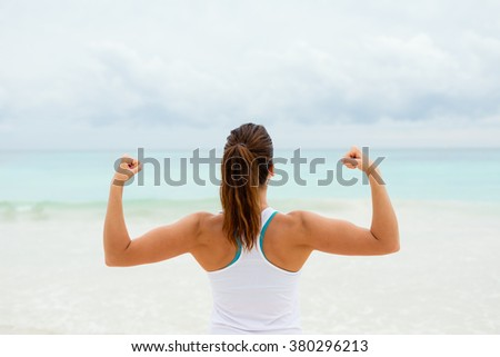Strong fitness woman showing arms biceps towards the sea. Healthy lifestyle motivation and success. - stock photo