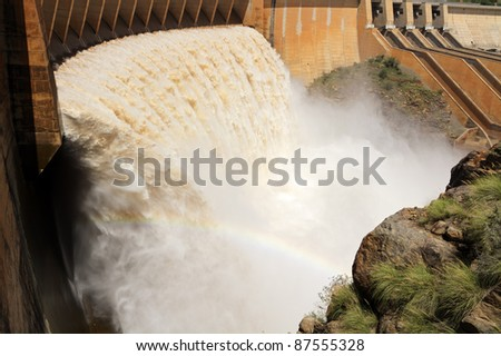 Strong flowing water released from the open sluice gates of a large dam - stock photo