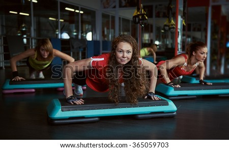 Strong girls doing push ups exercise on step boards in fitness class. Sport, power and recreation concept. - stock photo