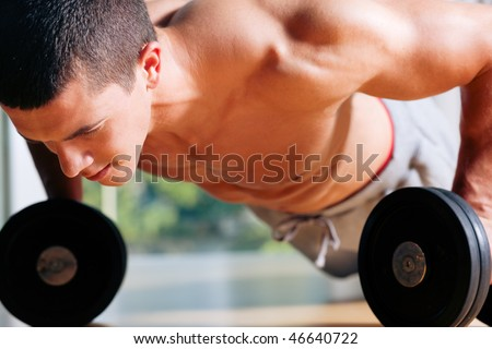 Strong, handsome man doing push-ups on dumbbells in a gym as bodybuilding exercise, training his muscles - stock photo