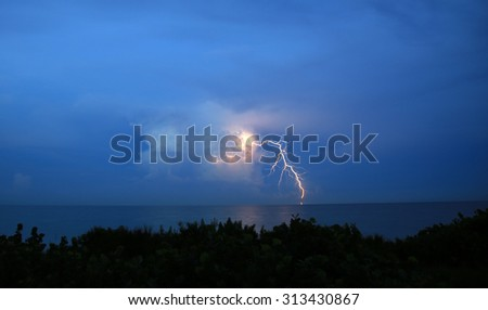 Strong lightning bolt from a cloud during a South Florida thunderstorm in the summer. - stock photo