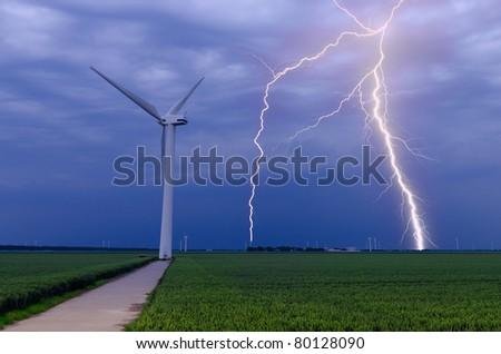Strong lightning threatening wind turbines in daylight - stock photo