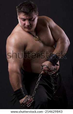 strong man breaks the chain on a black background - stock photo