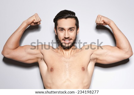 Strong man. Handsome young shirtless man keeping arms raised and looking at camera  while standing against grey background - stock photo