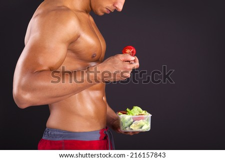Strong man holding a bowl of fresh salad on black background - stock photo