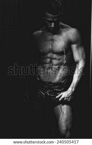 Strong man in chains posing under the rain, aqua studio .Low light .Shallow depth of field with focus on abdominals.  - stock photo