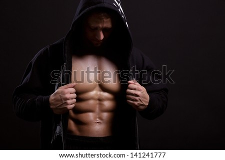 strong man in the hood showing his press on black background - stock photo