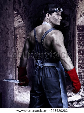 Strong man in the work wear holding the knife - stock photo