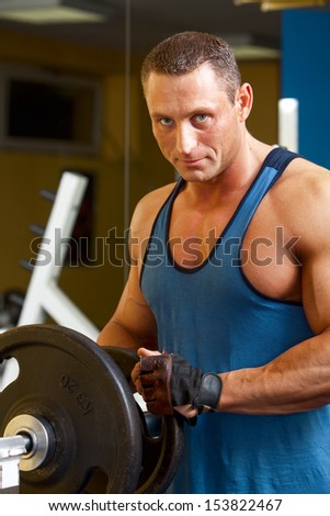 Strong man preparing his training machine in fitness club  - stock photo