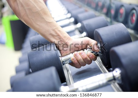 strong man's hand takes a heavy dumbbell in gym - stock photo
