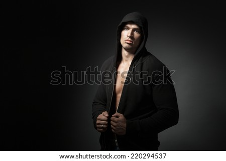 strong man wearing hoodie isolated on black background with copyspace - stock photo
