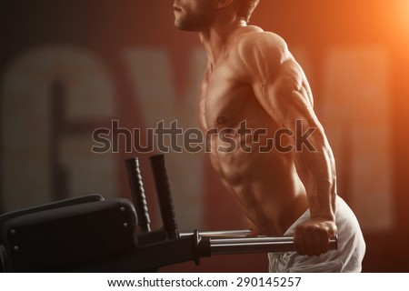 Strong muscular bodybuilder doing exercise on bars in the gym. Part of fitness body. Sports and fitness. Fitness man in the gym. - stock photo