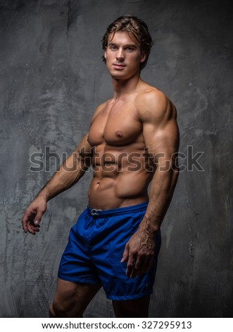 Strong muscular bodybuilder showing his body. Isolated on grey background. - stock photo
