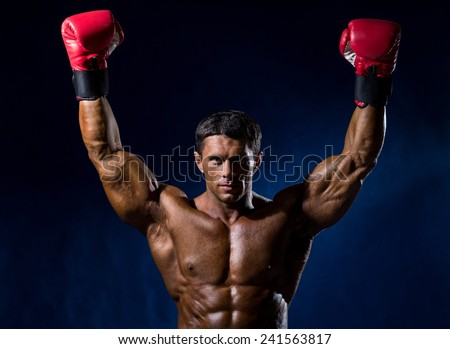 Strong muscular boxer in red boxing gloves raised his hands above his head. Victory in a boxing match - stock photo