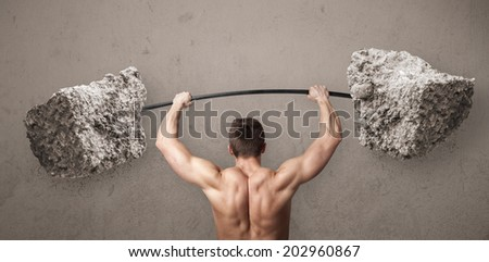 Strong muscular man lifting large rock stone weights - stock photo