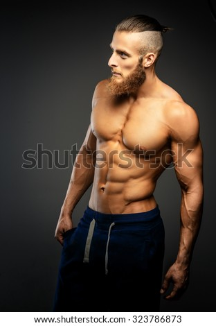 Strong muscular man with beard isolated on grey background. - stock photo