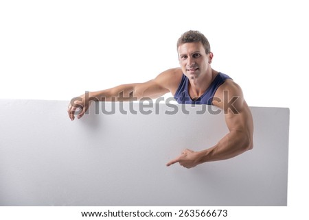 Strong muscular young man behind a blank horizontal white banner looking at camera, pointing at the copyspace for your text, on white - stock photo
