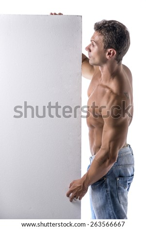 Strong muscular young man next to blank vertical white banner looking copyspace for your text, on white - stock photo