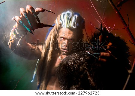 Strong scary werewolf with long nails in the wood. Demon with red eyes in the fog - stock photo