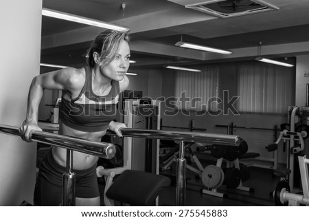 Strong, sexy chick in the gym. Blonde in sexy clothes posing in the gym. - stock photo