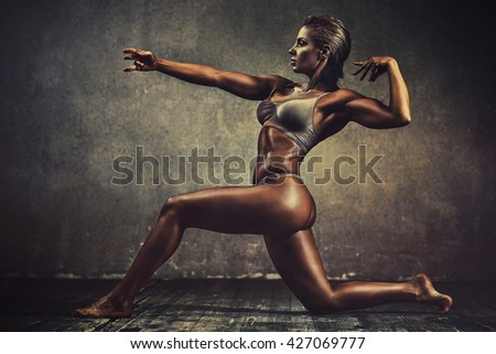 Strong sports woman on wall background. Vintage film style colors effect. - stock photo