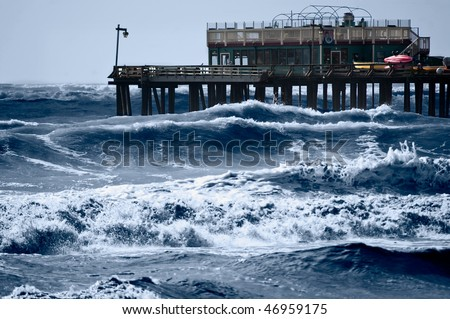 Strong storm driven waves pound the wharf - stock photo