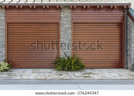 Strong vertical lines with landscape two single car garage doors - stock photo