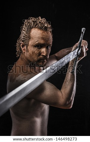 Strong warrior licking a big sword, covered in mud and naked - stock photo