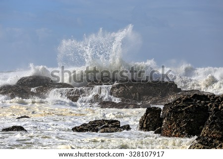 Strong waves breaking in a rocky beach from portuguese northwest coast - stock photo