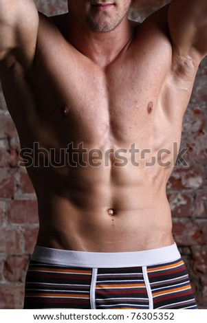 Strong wet sexy nude torso of young bodybuilder - stock photo