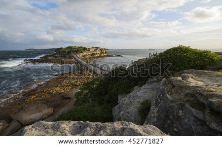 Strong wind at Bare Island Australia view from La Perouse with rock and green shrub in forground with afternoon sun and thin clouds in sky - stock photo